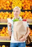 Flickan räcker den pappers- påsen med den läs- listan för nya grönsaker av produkter fotografering för bildbyråer