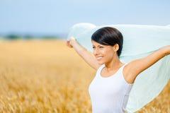 Flickan räcker den siden- halsduken mot rågfält royaltyfria foton