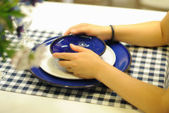 Flickan räcker innehav pläterar bordlägger på Royaltyfri Foto