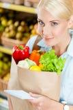 Flickan räcker paketet med den läs- listan för nya grönsaker av produkter arkivfoto