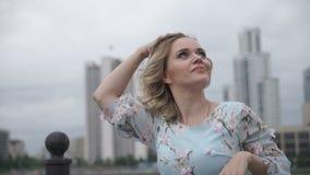 Flickan rätar ut hennes hår mot bakgrunden av skyskrapor arkivfilmer