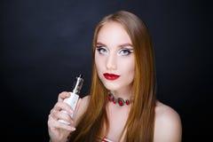 Flickan röker den elektroniska cigaretten Arkivbild
