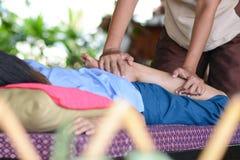 Flickan är avslappnande från massage av yrkesmässiga terapeuter Royaltyfri Foto