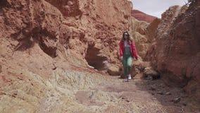 Flickan reser längs en ovanlig terräng röd jord och berg, som på Mars stock video