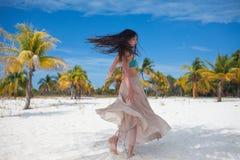 Flickan reser till havet och är lycklig Ung attraktiv brunettkvinnadans som vinkar hennes kjol mot tropiskt landskap arkivbilder
