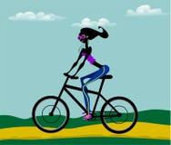 Flickan rider en cykel Arkivbilder