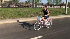 Flickan rider en cykel på en asfaltväg Bak hennes ryggsäck i en lastkorg per grupp av blommor arkivfilmer
