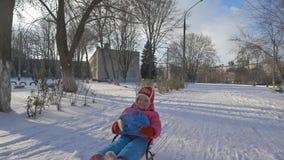 Flickan rider en släde till och med snön lager videofilmer