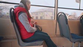 Flickan rider spårvagnen och att lyssna till musik lager videofilmer