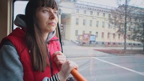 Flickan rider spårvagnen och ser ut fönstret stock video