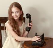 Flickan ringer på den gamla telefonen royaltyfri fotografi
