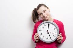 Flickan rymmer den runda klockan på vit bakgrund för objekttid för bakgrund begrepp isolerad white Y Arkivfoton