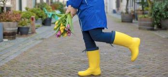 Flickan rymmer en bukett av nya tulpan i hennes händer, guling och rosa färger i en blå kappa och gula gummistöveler i en stad på royaltyfria bilder