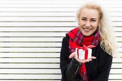 Flickan rymmer en gåva i deras händer och jublar Jul Royaltyfria Bilder