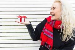 Flickan rymmer en gåva i deras händer och jublar Jul Arkivbilder