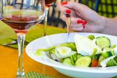 Flickan rymmer en gaffel och äter en grekisk sallad med rött vin i krogen arkivbilder