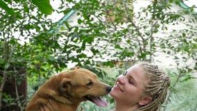 Flickan rymmer en hund på händer HD stock video
