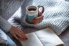 Flickan rymmer en kopp och läser boken royaltyfria bilder