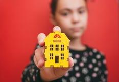 Flickan rymmer en liten gulinghemsymbol på en röd bakgrund och en fokus på byggande av det grunda djupet royaltyfria bilder