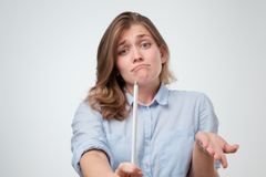 Flickan rymmer en rättfram vit blyertspenna i hennes hand och rycker på axlarna hennes skuldror helplessly fotografering för bildbyråer