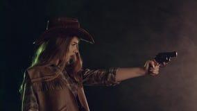 Flickan rymmer en revolver i henne händer och att sikta på rackaren Svart rökbakgrund långsam rörelse Slapp fokus stock video