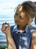 Flickan rymmer en skalbagge på en hand arkivbilder