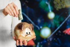 Flickan rymmer en spargris i hennes händer och sätter en dollar i den På bakgrunden av julgranen royaltyfri foto