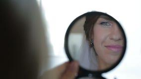 Flickan rymmer en spegel och att göra hennes smink arkivfilmer