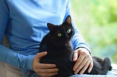 Flickan rymmer en svart katt arkivbild