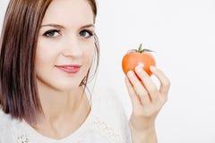 Flickan rymmer en tomat En ung kvinna rymmer en tomat i henne händer Arkivbilder