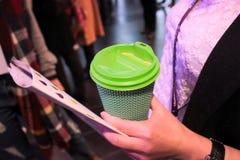 Flickan rymmer ett pappexponeringsglas av kaffe Arkivfoto