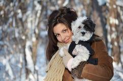 Flickan rymmer henne den gulliga klädda hunden Fotografering för Bildbyråer