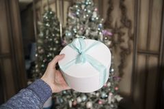 Flickan rymmer i handen en ask med den packade gåvan och på en bakgrund det dekorerade gran-trädet fotografering för bildbyråer