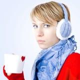 Flickan rymmer koppen av tea. Bilden har clippingbanan. Arkivfoto