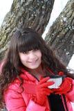 Flickan rymmer locket av termoset Arkivfoto