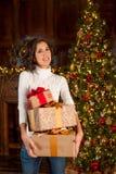 Flickan rymmer många julgåvor Arkivfoto