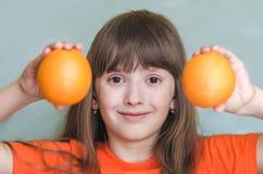 Flickan rymmer orange apelsiner och att le Fotografering för Bildbyråer