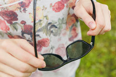 Flickan rymmer solglasögon hans händer i regn arkivfoton