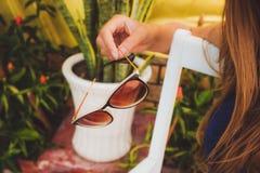 Flickan rymmer solglasögon i hand Arkivbilder
