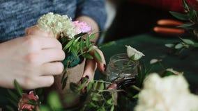 Flickan sätter in en grupp av blommor i en kruka av konstgjorda blommor arkivfilmer
