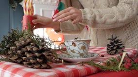Flickan sätter en kopp på det nya årets tabell lager videofilmer