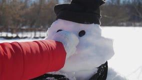 Flickan sätter in en näsa på snögubben Barnlekarna med en snögubbe Lycklig tid för vinter, unge på snö stock video
