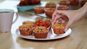 Flickan sätter en platta av muffin arkivfilmer