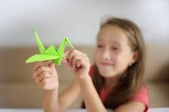 Flickan sätter origami från papper Royaltyfria Bilder