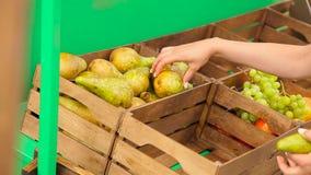 Flickan sätter päron i askar stock video