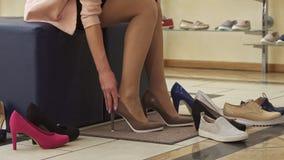Flickan sätter på bruna skor på shoppa arkivfoton