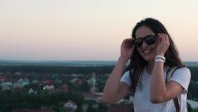 Flickan sätter på exponeringsglas på taket stock video