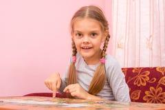 Flickan samlar en bild av pusslet, och sett in i ramen royaltyfri foto