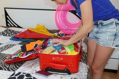 Flickan samlar in saker för ritten Emballageresväskor för ung kvinna på golv hemma Royaltyfria Foton