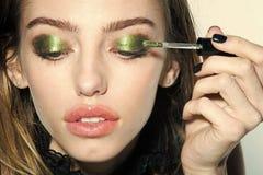 Flickan satte ögonskugga på ögon med borsten, ny teknik arkivfoto